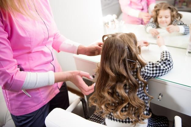 Stylista włosów przygotowuje córeczkę, robi loki fryzurę za pomocą lokówki. długie, jasnobrązowe, naturalne włosy.