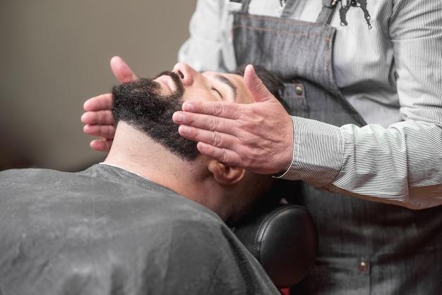 Stylista włosów stosujący po balsamie do golenia w sklepie fryzjerskim.