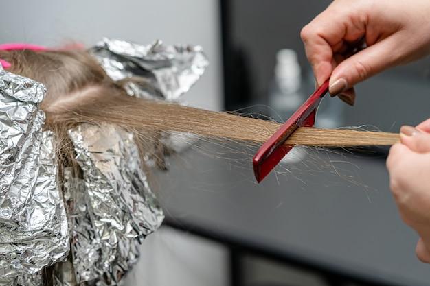 Stylista włosów utrwala fryzurę grzebieniem na cienkich pasmach. technika shatush do rozjaśniania włosów