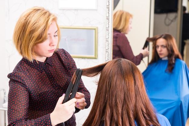 Stylista za pomocą prostownicy do stylizacji włosów klientów