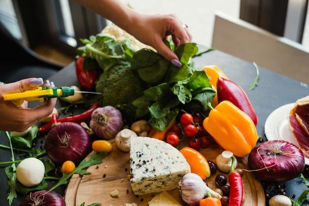 Stylista żywności spryskuje i przygotowuje warzywa. blogger w pracy. koncepcja projektowania hobby hobby