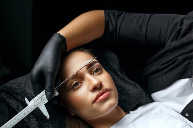Stylistka brwi mierząca linijką brwi przed zabiegiem makijażu permanentnego w gabinecie kosmetycznym