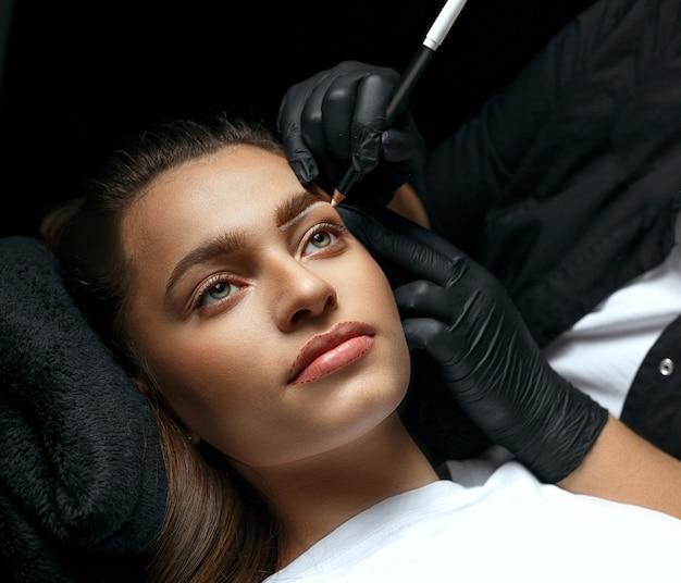 Stylistka brwi modelująca brwi białą kredką przed zabiegiem makijażu permanentnego