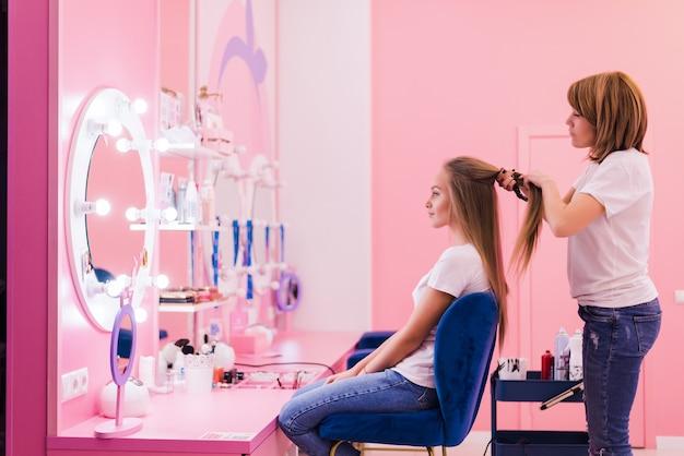 Stylistka kręcąca włosy brązowowłosej kobiety w salonie