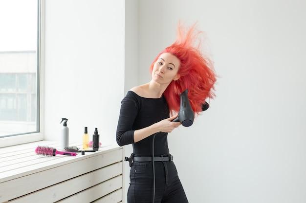 Stylistka, moda, fryzjer, koncepcja ludzie - kobieta susząca kolorowe włosy.