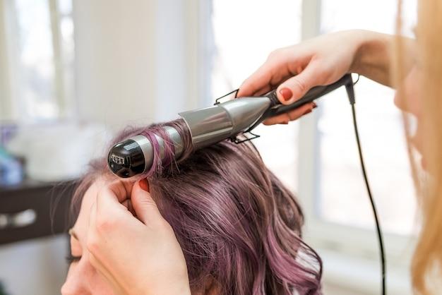 Stylistka robi fryzurę dla dziewczynki o kolorowych włosach, lokach na liliowych włosach