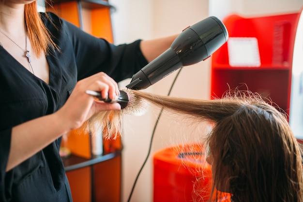Stylistka susząca włosy suszarką, kobieta fryzjerska w salonie fryzjerskim.