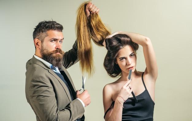 Stylizacja i strzyżenie brody. sprawienie, by fryzura wyglądała idealnie w salonie fryzjerskim. ostry jak brzytwa. narzędzia fryzjerskie na szarej ścianie z miejsca na kopię.