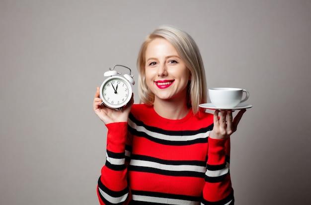 Stylizowana blondynka w czerwonym swetrze z budzikiem i filiżanką kawy na szarej ścianie