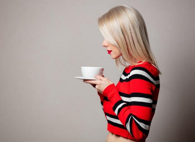 Stylizowana blondynka w czerwonym swetrze z filiżanką kawy na szarej ścianie