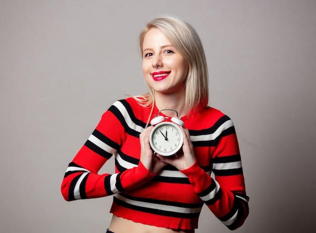 Stylizowana kobieta w czerwonym swetrze z budzikiem na szarej ścianie