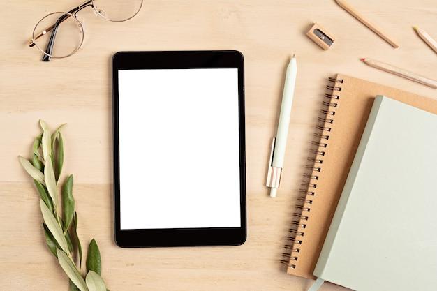 Stylizowana minimalna makieta pulpitu z kolorowym stacjonarnym, cyfrowym tabletem, notatnikiem. freelancer, koncepcja blogera mediów społecznościowych. leżał na płasko, widok z góry, miejsce na kopię.