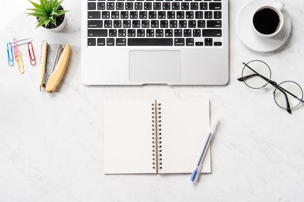 Stylizowane biurko z czystego marmuru ze smartfonem, laptopem, okularami i kawą, projekt obszaru roboczego, makieta, widok z góry, flatlay, copyspace, zbliżenie