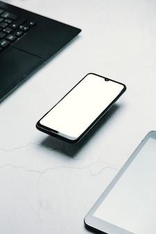 Stylizowane czyste marmurowe biurko do pracy ze smartfonem, laptopem, okularami i filiżanką kawy, projekt obszaru roboczego, makieta, widok z góry, układ płaski, miejsce do kopiowania, zbliżenie