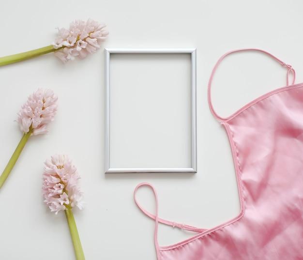 Stylizowane kobiece mieszkanie z pustą ramką na zdjęcia, jedwabną bielizną i różowymi kwiatami na białym tle