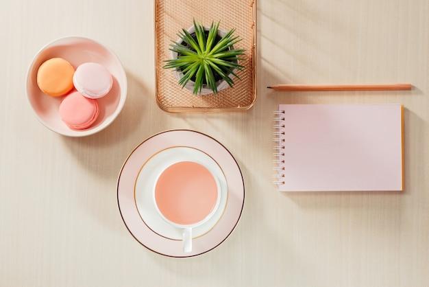 Stylizowane stock photography beżowy stół biurowy z pustym notatnikiem, makaronikiem, dostawami i filiżanką kawy