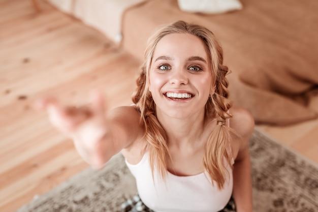 Stylizowane warkocze. atrakcyjna zadowolona kobieta unosząca rękę, pokazująca szeroki uśmiech i nietuzinkowe warkocze