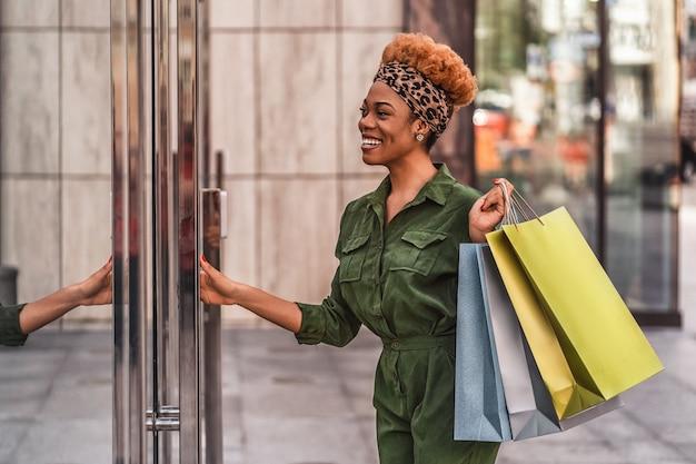 Stylowa afro american kobieta trzymając torby na zakupy i otwierając drzwi centrum handlowego w mieście, uśmiechając się