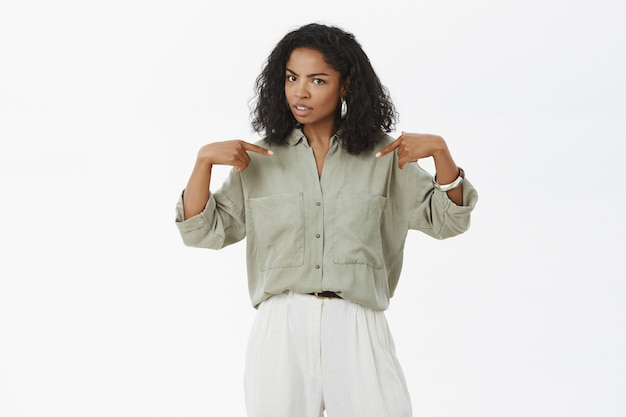 Stylowa afroamerykanka wskazująca na siebie z niepewnym wyrazem twarzy