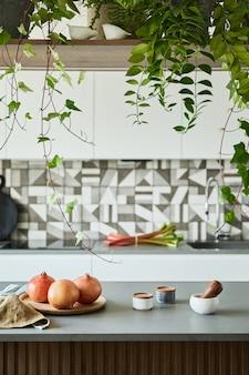 Stylowa aranżacja kuchni z wyspą kuchenną. miejsce pracy z akcesoriami kuchennymi w tle. kreatywne ściany z drewnianymi panelami. minimalistyczny styl koncepcja miłości do roślin.