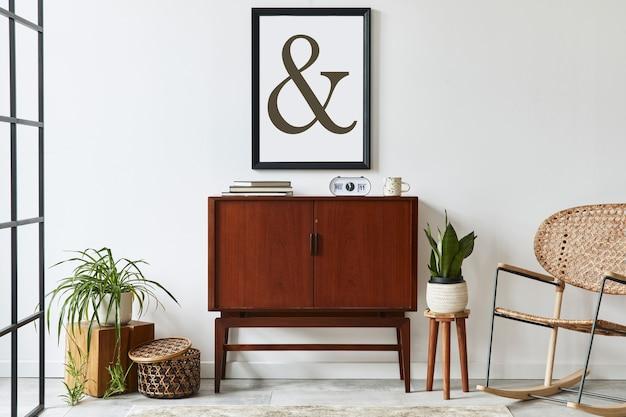 Stylowa aranżacja wnętrza salonu z drewnianą komodą retro, krzesłem, rośliną, rattanową dekoracją, kostką i eleganckimi dodatkami osobistymi. makieta ramki plakatowej na białej ścianie. szablon.