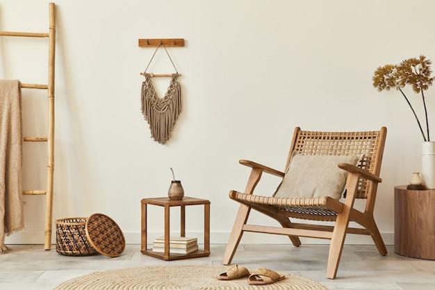 Stylowa aranżacja wnętrza salonu z drewnianym fotelem, stolikiem kawowym, meblami, rattanową dekoracją, suszonymi kwiatami i eleganckimi dodatkami osobistymi. skopiuj przestrzeń biała ściana. szablon.