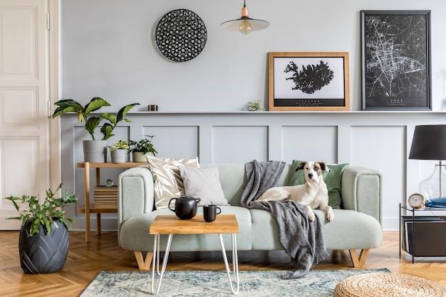 Stylowa aranżacja wnętrza salonu z nowoczesną miętową sofą, drewnianą konsolą, kostką, stolikiem kawowym, lampą, rośliną, ramą plakatową, poduszkami, pledem, dekoracją i eleganckimi dodatkami w wystroju domu.