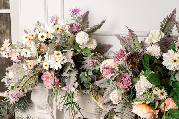 Stylowa aranżacja wnętrza salonu ze sztucznymi kwiatami i kominkiem.
