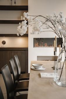 Stylowa aranżacja wnętrza strefy jadalni ze stołem i krzesłami w nowoczesnym mieszkaniu
