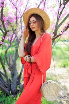 Stylowa artystyczna dziewczyna pozuje w koralowej sukience i słomkowym kapeluszu w pobliżu kwitnącej wiśni w wiosennym parku.