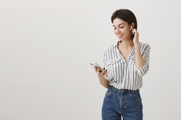 Stylowa atrakcyjna kobieta trzymając telefon komórkowy i słuchanie muzyki w słuchawkach bezprzewodowych