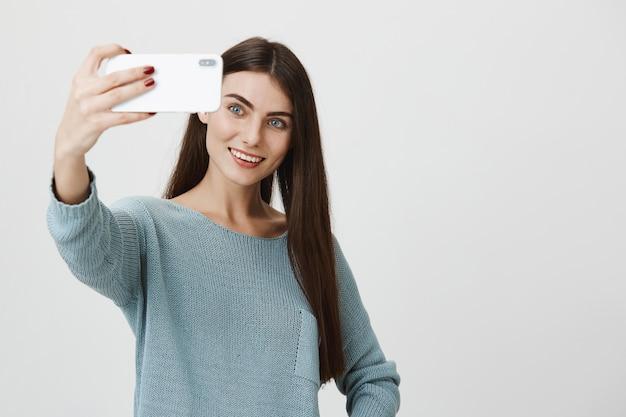 Stylowa atrakcyjna kobieta uśmiechnięta, biorąc selfie