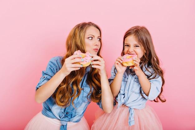 Stylowa atrakcyjna mama gotowała pączki z kręconą córką i próbowała ich na różowym tle. portret dziewczynki z piękną mamą w dżinsowej koszuli, jedząc pyszne słodycze na tea party