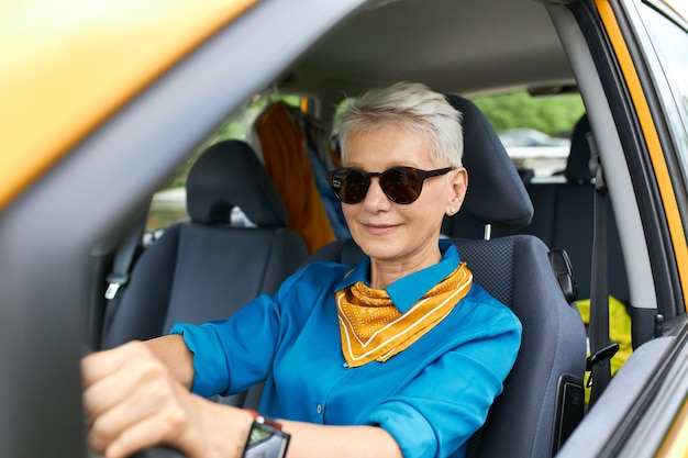 Stylowa atrakcyjna, ruchliwa kobieta w średnim wieku, ubrana w okulary przeciwsłoneczne i zegarek na rękę, idąca na zakupy, prowadząca swój nowy samochód, wyglądająca pewnie
