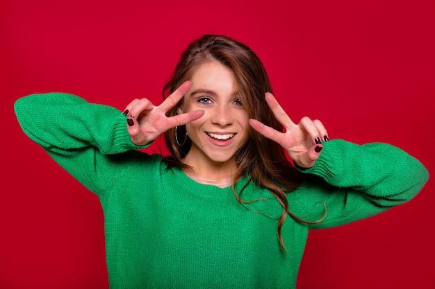 Stylowa atrakcyjna szczęśliwa młoda dama pokazuje znak pokoju palcami mrugając na białym tle na czerwonym tle, szczęśliwe emocje, odizolowane tło, szczęście
