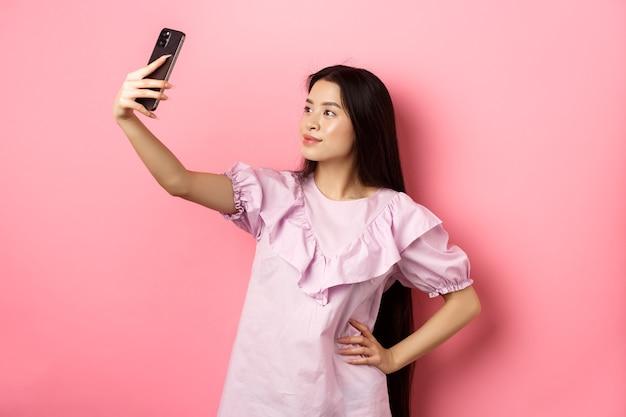 Stylowa azjatka bierze selfie i uśmiecha się, pozuje do zdjęcia w mediach społecznościowych, stojąc w sukience na różowym tle.