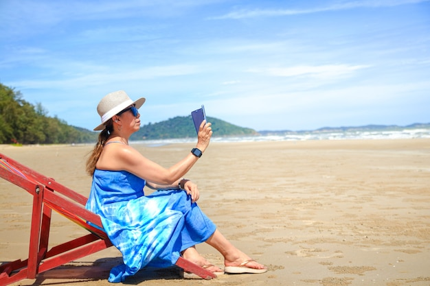 Stylowa azjatka ubrana w długą niebieską sukienkę. opalanie się nad morzem, trzymając smartfon w ręku, aby robić zdjęcia pięknej, naturalnej scenerii podróż nad morze w tajlandii, turystyka