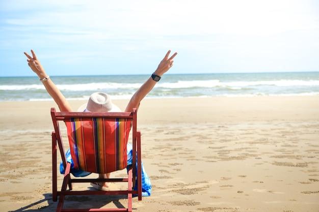 Stylowa azjatka ubrana w długą niebieską sukienkę. usiądź w słońcu nad morzem i podziwiaj piękne naturalne krajobrazy. turyści śpią na płóciennych łóżkach z podniesionymi obydwoma rękami, chętnie odwiedzają tajskie morze.