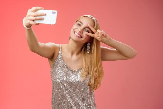 Stylowa, bajeczna glamour młoda blond kobieta w błyszczącej srebrnej sukience przechylającej głowę beztroski pokaz pokoju gest znak zwycięstwa wydłużenie ramienia trzymającego smartfona przy selfie nagrywanie wideo post online