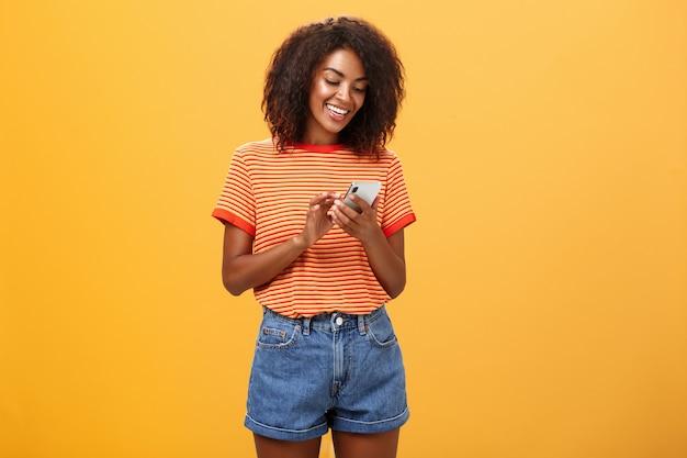 Stylowa beztroska dziewczyna wysyłająca sms-y do przyjaciółki, stojąc zadowolona nad pomarańczową ścianą