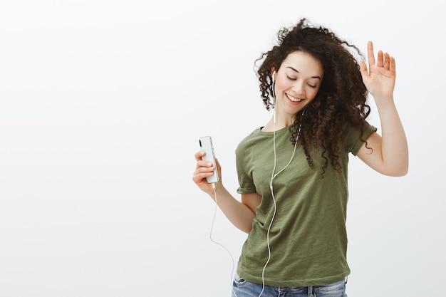 Stylowa beztroska europejska dziewczyna z kręconymi włosami