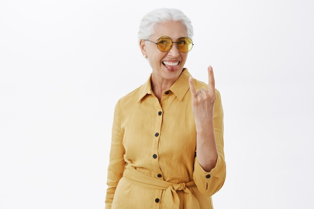 Stylowa beztroska starsza kobieta w okularach przeciwsłonecznych pokazująca rock-n-rollowy gest i uśmiechnięta, dobra zabawa