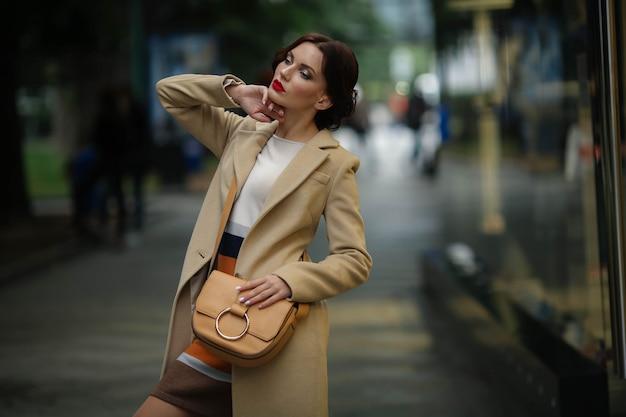 Stylowa bizneswoman 25 lat w białym płaszczu na tle ulicy ze sklepami