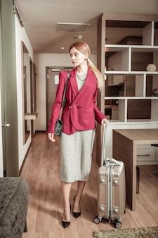 Stylowa bizneswoman. szczupła, stylowa kobieta po ważnej podróży służbowej do swojego pokoju hotelowego