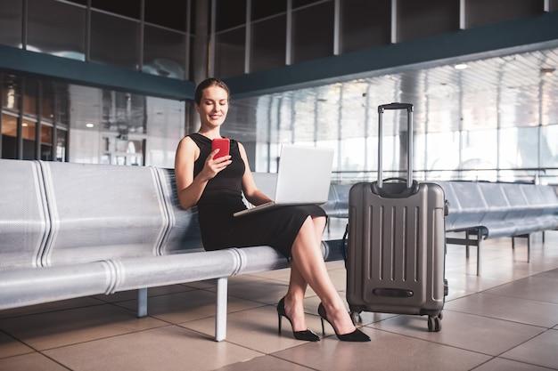 Stylowa bizneswoman z bagażem na lotnisku