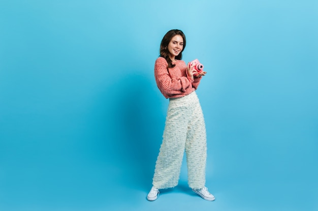 Stylowa blogerka pozuje z różowym aparatem instax. dama w białych spodniach uśmiecha się słodko na niebieskiej ścianie.