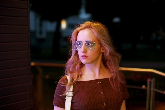 Stylowa blond kobieta w modnej odzieży i okularów, ciesząc się życiem nocnym w mieście.