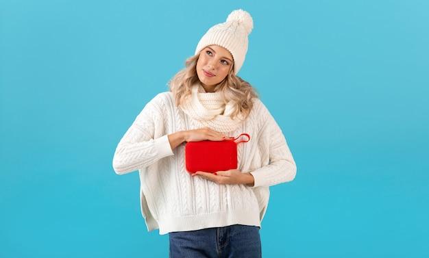 Stylowa blond uśmiechnięta piękna młoda kobieta trzyma bezprzewodowy głośnik słuchania muzyki szczęśliwy na sobie biały sweter i czapka z dzianiny, pozowanie na niebiesko