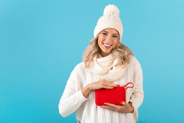 Stylowa blond uśmiechnięta piękna młoda kobieta trzymająca bezprzewodowy głośnik słuchający muzyki szczęśliwa na sobie biały sweter i czapka z dzianiny moda w stylu zimowym pozowanie na niebieskiej ścianie