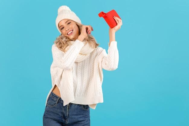 Stylowa blond uśmiechnięta piękna młoda kobieta trzymająca głośnik bezprzewodowy słuchający muzyki szczęśliwy taniec na sobie biały sweter i czapkę z dzianiny zimowy styl pozowanie fashion